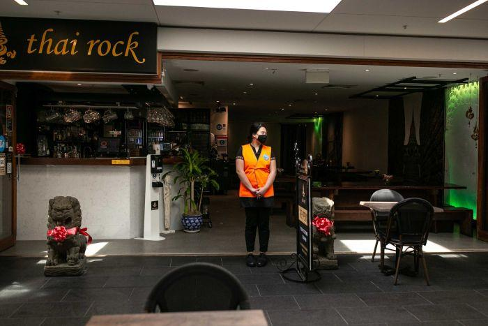 A woman with a face mask stands between several empty tables