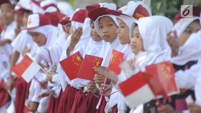 Sejumlah murid menyambut kedatangan PM China Li Keqiang di kawasan Istana Bogor, Senin (7/5). Li juga akan membahas peningkatan hubungan kerja sama perdagangan Indonesia-China. (Merdeka.com/Arie Basuki)