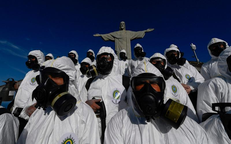 Soldiers of the Brazilian Armed Forces are seen during the disinfection procedures of the Christ The Redeemer statue at the Corcovado mountain prior to the opening of the touristic attraction on August 15 - Mauro Pimentel/AFP