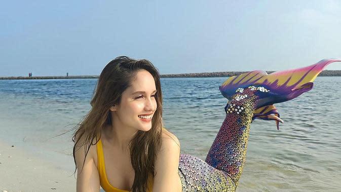 Dua foto yang dibagikan tersebut, Cinta tampak cantik memesona berdandan mermaid di pinggir pantai. Riasan wajah simple dan rambut dibiarkan terurai. Satu foto tersenyum ke arah laut dan yang satu dengan mata terpejam memandang ke atas langit. (Instagram/claurakiehl)