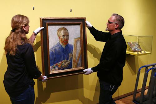 Curators hang an 1888 self-portrait of Vincent Van Gogh in which he painted himself behind a canvas, brushes and palette in hand, the final painting before the reopening after a seven-month renovation, at Van Gogh museum in Amsterdam, Netherlands, Wednesday, May 1, 2013. Displayed on the right are a wooden palette and paints that Van Gogh used in 1890. (AP Photo/Vincent Jannink)