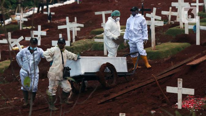 Petugas menunggu waktu pemakaman jenazah yang akan dimakamkan dengan protokol COVID-19 di TPU Pondok Ranggon, Jakarta, Sabtu (17/10/2020). Petugas terpaksa menggunakan gerobak dikarenakan kondisi tanah yang lengket dan licin akibat diguyur hujan. (Liputan6.com/Helmi Fithriansyah)
