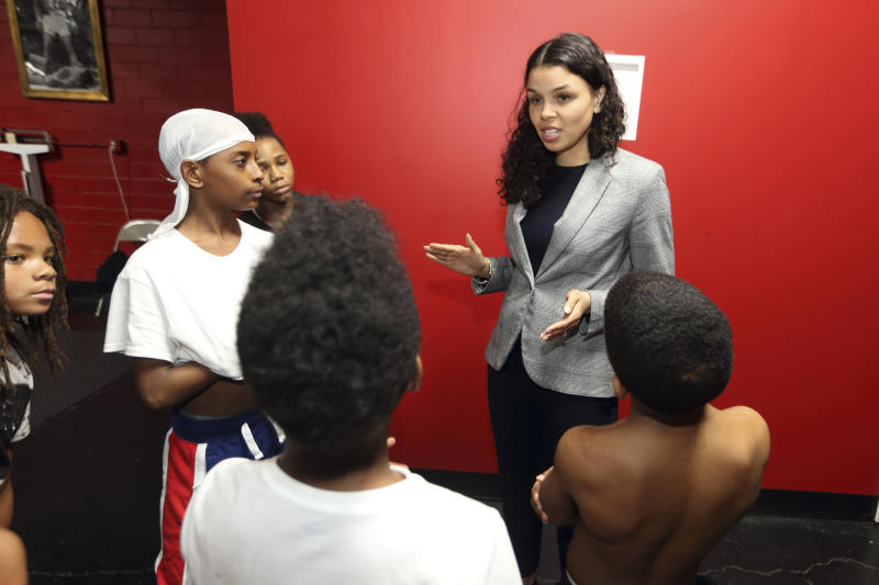 FILE—In this March 10, 2020, file photo, Morgan Harper, center, Democratic candidate for Ohio's third congressional district running against Democratic four-term incumbent Joyce Beatty, talks with End the Violence participants at Elite Boxing Gym in Columbus, Ohio. In Ohio, candidates such as Harper and other congressional hopefuls Kate Schroder and Nikki Foster nearly emptied their campaign coffers in the closing days before March 17, and now are focusing on social media and phone banks to keep up their campaigns while awaiting clarity on when the primary will end amid the coronavirus stay-home orders. (AP Photo/Paul Vernon, File)