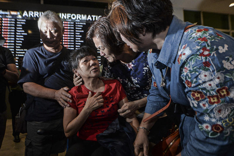 Malaysian victim of the Lombok earthquake, How Geok Lan (in red), is greeted by her former schoolmates of the same batch born in 1963 after arriving at KLIA2 in Sepang March 19, 2019. — Picture by Shafwan Zaidon