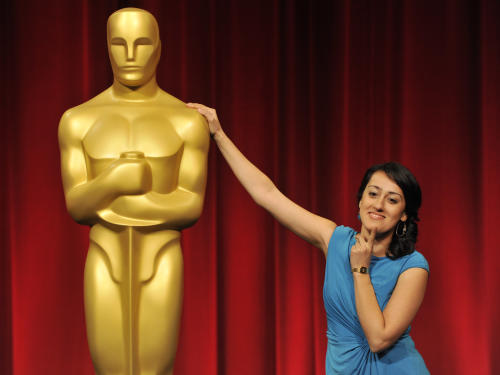 "Filmmaker Talkhon Hamzavi of Zurich University of the Arts in Switzerland, a nominee in the Foreign Film Category for her film ""Parvaneh,"" poses alongside an Oscar statue before the Academy of Motion Picture Arts and Sciences 40th Student Academy Awards at the Samuel Goldwyn Theater on Saturday, June 8, 2013 in Beverly Hills, Calif. (Photo by Chris Pizzello/Invision/AP)"