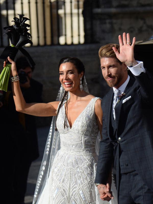 Bek Real Madrid, Sergio Ramos dan Pilar Rubio menyapa awak media setelah upacara pernikahan mereka di Sevilla, Spanyol (15/6/2019). Ramos resmi menikahi kekasihnya Pilar Rubio setelah berpacaran sejak 2012. (AFP Photo/Cristina Quicler)