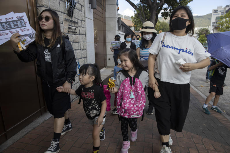 "Emily Ku, right, joins a protest against the use of tear gas with her sister Kari Ku, left, and their children in Hong Kong Saturday, Nov. 23, 2019. Chanting ""No more tear gas,"" dozens of Hong Kong families with young children are marching to oppose the government's handling of protests on the eve of keenly contested local elections. (AP Photo/Ng Han Guan)"