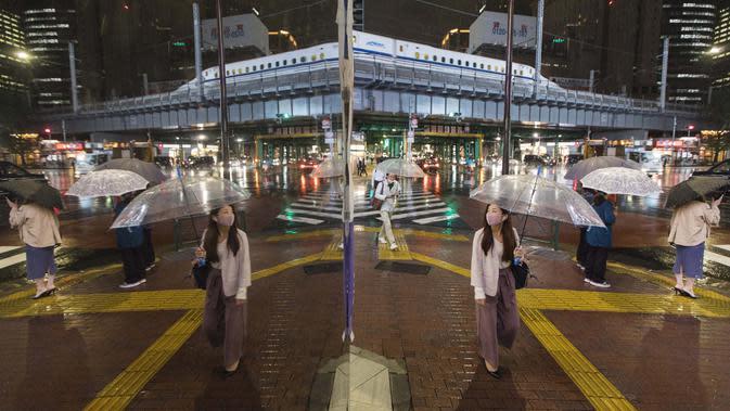 Orang-orang yang terlihat dalam refleksi berjalan melintasi persimpangan di tengah hujan di Tokyo pada hari Kamis (8/10/2020). (AP Photo/Hiro Komae)