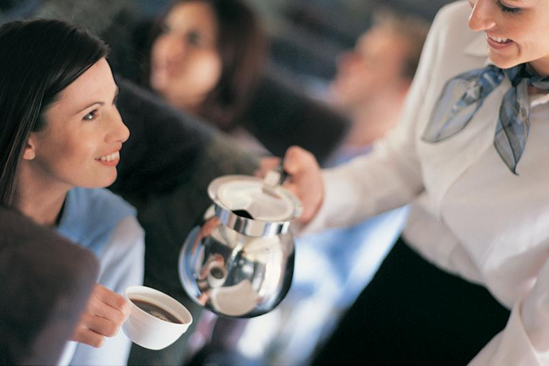 Female Passenger Being Served Coffee By An Air Stewardess