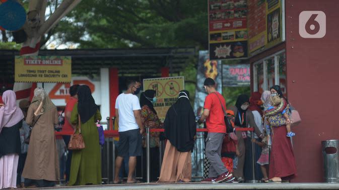 Wisatawan masuk ke Taman Mini Indonesia Indah, Jakarta, Kamis (20/8/2020). Warga memanfaatkan momen libur panjang Tahun Baru islam 1442 H ke tempat rekreasi yang dekat karena masih situasi pandemi Corona (COVID-19) dengan menjaga protokol kesehatan. (merdeka.com/Imam Buhori)