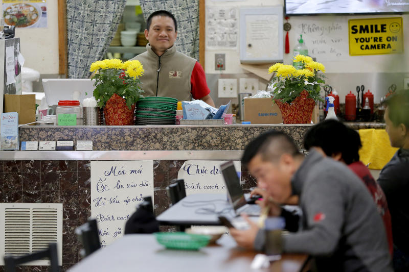In this Feb. 13, 2020, photo, restaurant owner Phong Nguy watches from his counter as customers eat lunch in the food court at the Mekong Plaza in the Asian district, in Mesa, Ariz. Arizona's freshly crowned Asian District was deep into organizing its night market when news broke that a case of the illness known as COVID-19 was confirmed at nearby Arizona State University. Xenophobic comments on social media and phone calls started almost immediately, according to Arizona Asian Chamber of Commerce CEO Vicente Reid. (AP Photo/Matt York)