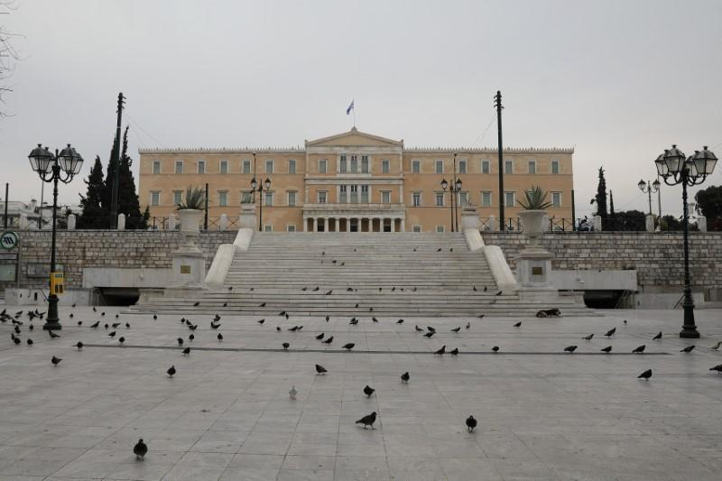 Pigeons flock on the empty Syntagma square with the parliament building in the background, following an outbreak of the coronavirus disease (COVID-19), in Athens