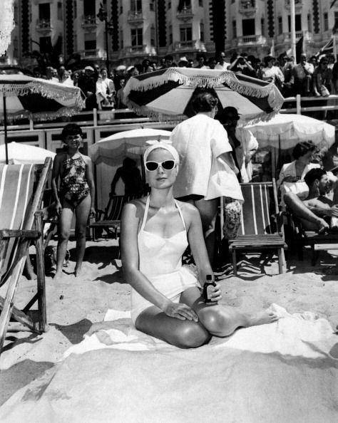 <p>Grace Kelly lounges on a beach towel in France, circa 1955.</p>