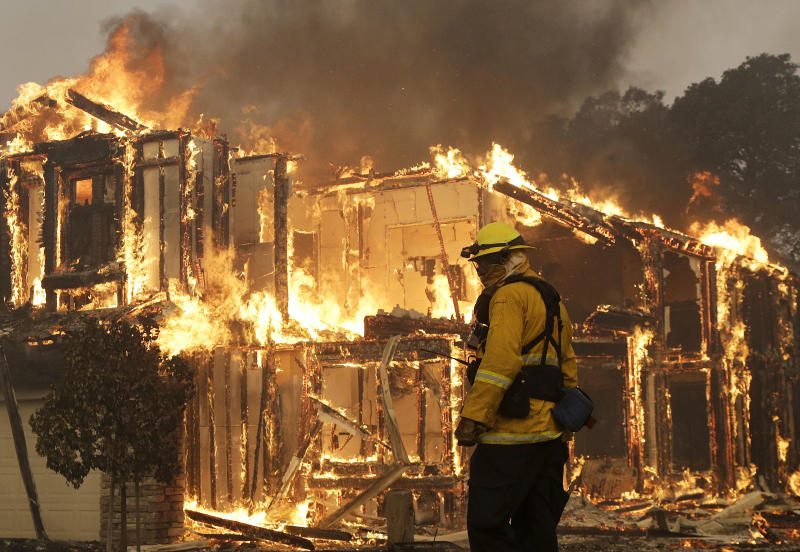 FILE - In this Oct. 9, 2017, file photo, a firefighter monitors a house burning in Santa Rosa, Calif. California power regulators slapped Pacific Gas and Electric with a $2.1 billion fine for igniting a series of deadly wildfires that landed the beleaguered utility in bankruptcy. The record penalty imposed Thursday, Feb. 27, 2020, in a an administrative law judge's decision boosts the punishment that had been agreed upon in a $1.7 billion settlement announced in December. The increased punishment includes a $200 million payment earmarked for the people who lost family and property in catastrophic wildfires caused by PG&E's outdated electrical grid and negligence during 2017 and 2018. (AP Photo/Jeff Chiu, File)