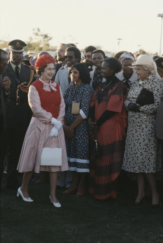 During a royal state visit to Botswana, Her Majesty stole the spotlight in a red pussy-bow dress complete with a matching sleeveless knit and floral hat. <em>[Photo: Getty]</em>
