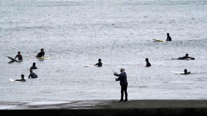 Seorang pria memancing saat peselancar berselancar di pantai Katase-kaigan yang berangin, Fujisawa, Prefektur Kanagawa, selatan Tokyo, Jepang, Kamis (24/9/2020). Badai Tropis Dolphin bergerak di sepanjang pantai Pasifik Jepang. (AP Photo/Eugene Hoshiko)