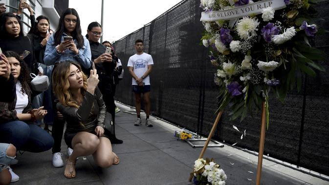 Fans Kobe Bryant berduka saat berkumpul di depan Staples Center, Los Angeles Lakers (26/1/2020). Dunia olah raga terkejut atas kabar buruk itu untuk kemudian serempak menyampaikan duka cita. (AP Photo/Chris Pizzello)
