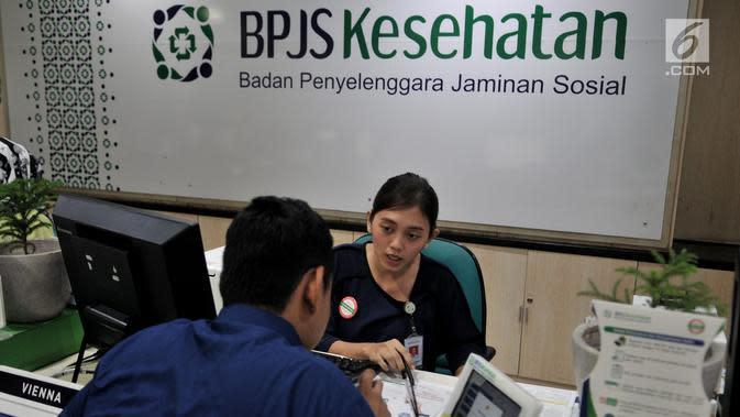 Petugas BPJS Kesehatan melayani warga di kawasan Matraman, Jakarta, Rabu (28/8/2019). Menkeu Sri Mulyani mengusulkan iuran peserta kelas I BPJS Kesehatan naik 2 kali lipat yang semula Rp 80.000 jadi Rp 160.000 per bulan untuk JKN kelas II naik dari Rp 51.000 menjadi Rp110.000 per bulan. (merdeka.com