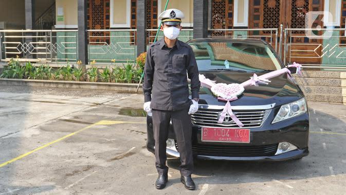 Petugas Muhamad Kholiq berpose seusai mengantarkan pengantin di kawasan Bekasi, Jawa Barat, Sabtu (12/9/2020). Wakil Wali Kota Bekasi menyediakan fasilitas gratis mobil dinas pada hari Sabtu dan Minggu untuk antar jemput pengantin saat pandemi COVID-19. (Liputan6.com/Herman Zakharia)