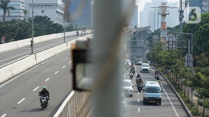 Pengendara sepeda motor melintasi Jalan Layang Non-Tol (JLNT) Kampung Melayu-Tanah Abang di Jakarta, Selasa (9/6/2020). Kurangnya penindakan pelanggar lalu lintas menyebabkan sebagian pemotor nekat menerobos JLNT, meskipun perilaku tersebut membahayakan keselamatan. (Liputan6.com/Immanuel Antonius)