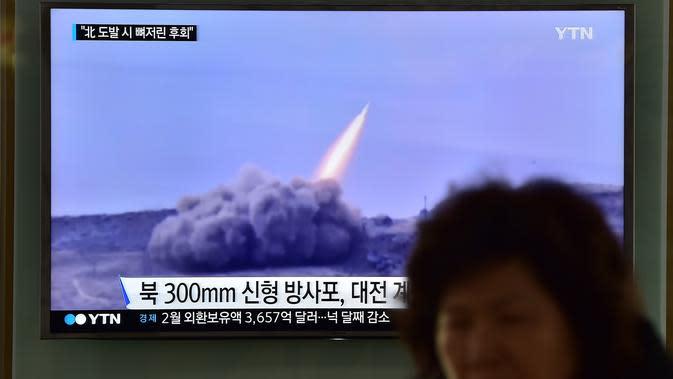 Seorang wanita melewati layar yang menyiarkan berita tentang peluncuran roket Korut, di stasiun kereta di Seoul, Korsel, Jumat (4/3). Kim Jong-Un memerintahkan pasukannya menyiagakan senjata nuklir untuk bisa digunakan kapan saja. (AFP PHOTO/Jung YEON-JE)