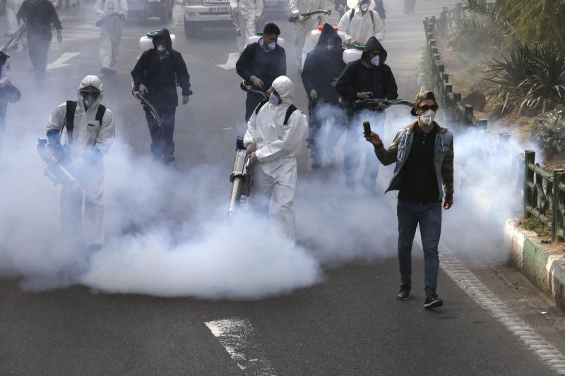 In this Friday, March 13, 2020 photo, firefighters disinfect a square against the new coronavirus as a man takes film, in western Tehran, Iran. Local media reported Thursday March 26, 2020, that nearly 300 people have been killed and more than 1,000 sickened by ingesting toxic methanol across the Islamic Republic out of the false belief it kills the virus. (AP Photo/Vahid Salemi)