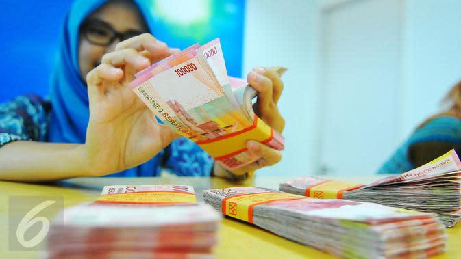 Petugas Bank tengah menghitung uang rupiah di Bank BRI Syariah, Jakarta, Selasa (28/2). Nilai tukar rupiah terhadap dolar Amerika Serikat (AS) melemah tipis pada perdagangan Selasa pekan ini. (Liputan6.com/Angga Yuniar)