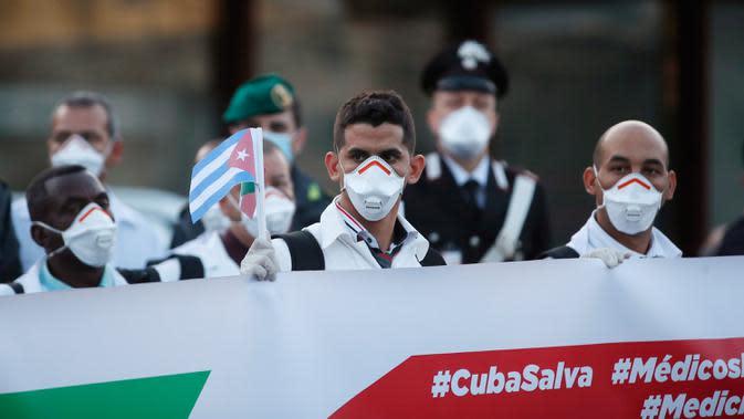 Petugas medis dan paramedis dari Kuba berpose setibanya di bandara Malpensa di Milan, Italia, Minggu (22/3/2020). Kedatangan tim medis Kuba membantu Italia mengendalikan pandemi virus Corona, salah satu negara terkaya di Eropa, merupakan yang pertama kali terjadi. (AP/Antonio Calanni)