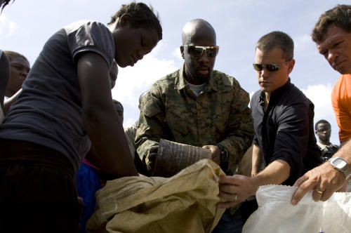 "FILE - In this Sept. 14, 2008 file photo, actor Matt Damon, second right and Haitian-born singer Wyclef Jean, center, distribute food to flood victims after four tropical storms hit the area in Gonaives, Haiti. Jean's autobiography ""Purpose"" goes on sale Tuesday, Sept. 18, 2012. (AP Photo/Ramon Espinosa, File)"