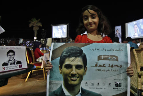 "A Palestinian girl carries a poster of singer Mohammed Assaf, 23, while watching the televised performance of the Palestinian finalist on the Arab Idol talent show, in Gaza City, Friday, June 21, 2013. Assaf, Gazan's powerful voice has propelled him to the final at the ""Arab Idol"" in a TV talent contest choosing a winner in Beirut on Saturday. He is the first Palestinian to qualify for ""Arab Idol."" The poster, front, reads ""Vote to Arab Idol Mohammed Assaf,"" ""we have the same dream, our dream is close,"" and ""Vote and the Bank of Palestine votes with you."" (AP Photo/Adel Hana)"