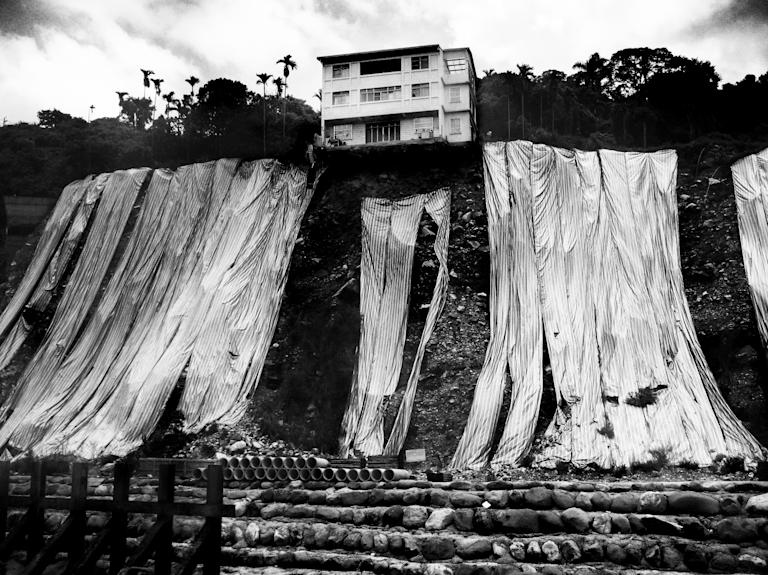 Youth 'Environment' winner: Xu Wei Shou, Taiwan. 'Nature's fightback' shows a house tottering on teetering on the edge of a cliff (Xu Wei Shou, Taiwan, Winner, Environment, Youth Competition, 2013 Sony World Photography Awards)