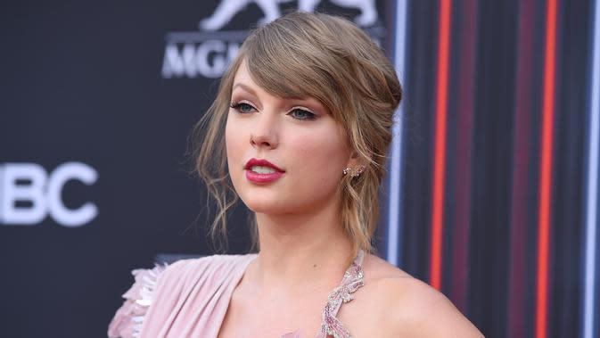 Penyanyi Taylor Swift berpose saat tiba menghadiri Billboard Music Awards di MGM Grand Garden Arena di Las Vegas (20/5).Taylor Swift tampil cantik dengan gaun Versace warna merah muda dengan belahan paha tinggi. (AP Photo/Jordan Strauss)