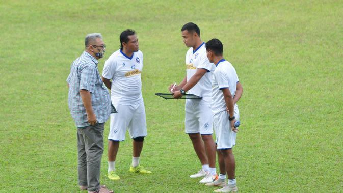 Tiga asisten pelatih Arema FC, Charis Yulianto, Singgih Pitono, dan Kuncoro, berdiskusi di depan GM Arema, Ruddy Widodo, saat sesi latihan perdana yang digelar di Stadion Kanjuruhan, Malang, Senin (3/8/2020). (Bola.com/Iwan Setiawan)