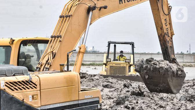 Petugas dari Dinas Bina Marga menggunakan kendaraan alat berat saat menyelesaikan penggarapan lahan untuk dijadikan lokasi pemakaman khusus Covid-19 di Rorotan, Jakarta, Selasa (29/9/2020). Lokasi pemakaman khusus Covid-19 memiliki Lahan seluas 2 hektare. (merdeka.com/Iqbal S. Nugroho)