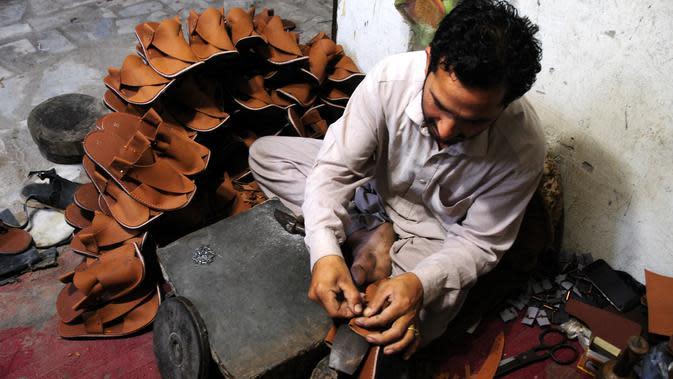 Seorang pembuat sepatu asal Pakistan membuat sepatu tradisional yang dikenal sebagai