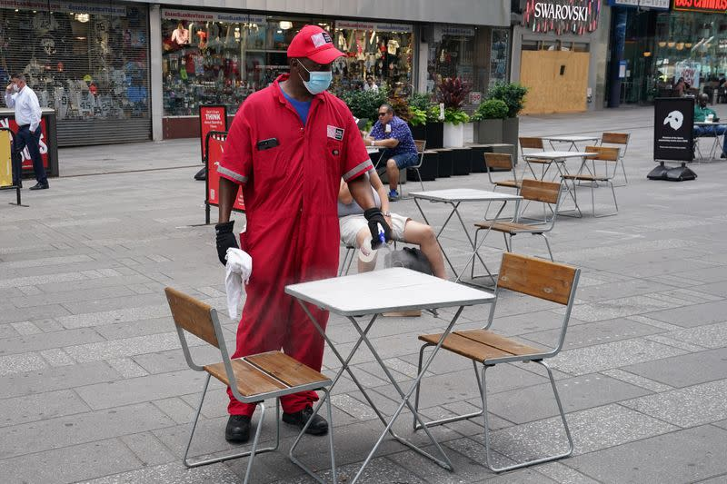 A worker cleans and disinfects a table in Times Square in the Manhattan borough of New York City
