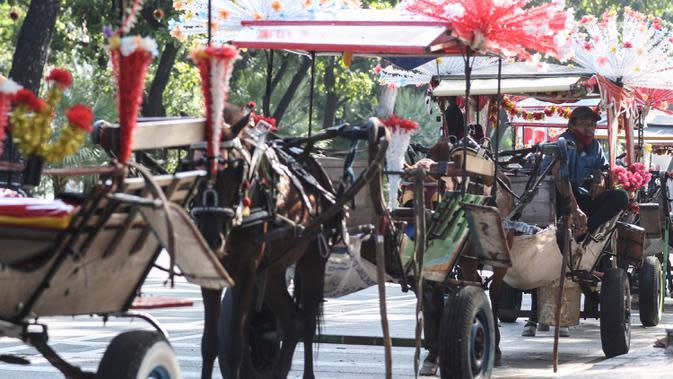 Kusir menunggu calon penumpang delman di kawasan IRTI Monas, Jakarta, Jumat (21/8/2020). Jasa sewa delman untuk warga berkeliling kawasan Monas tersebut bertarif Rp 50 ribu hingga Rp100 ribu. (Liputan6.com/Johan Tallo)