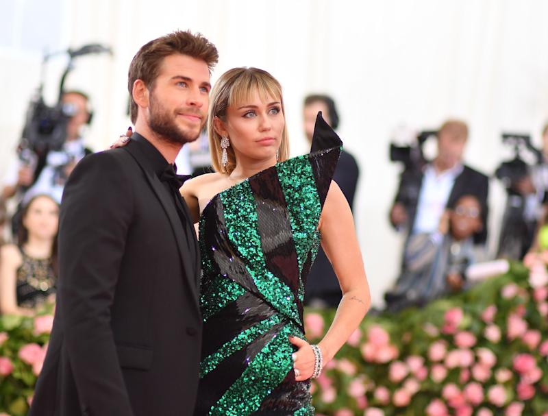 """Miley Cyrus (R) and Liam Hemsworth arrive for the 2019 Met Gala at the Metropolitan Museum of Art on May 6, 2019, in New York. - The Gala raises money for the Metropolitan Museum of Arts Costume Institute. The Gala's 2019 theme is Camp: Notes on Fashion"""" inspired by Susan Sontag's 1964 essay """"Notes on Camp"""". (Photo by ANGELA WEISS / AFP) (Photo credit should read ANGELA WEISS/AFP/Getty Images)"""