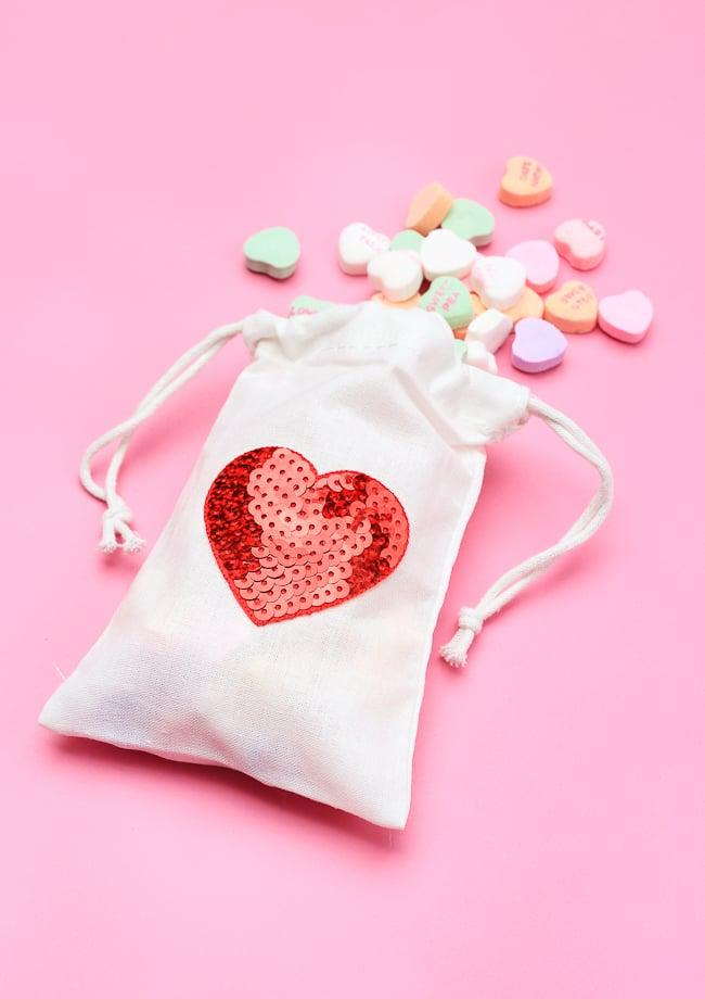 """<p>Although The Crafted Life fills these <a href=""""https://thecraftedlife.com/10-minutes-or-less-diy-sequin-heart-treat-bags/"""" target=""""_blank"""" class=""""ga-track"""" data-ga-category=""""Related"""" data-ga-label=""""https://thecraftedlife.com/10-minutes-or-less-diy-sequin-heart-treat-bags/"""" data-ga-action=""""In-Line Links"""">DIY sequin heart treat bags</a> with conversation hearts, you could easily stuff 'em with pencil erasers or a small toy or use them as the cutest envelope for a paper valentine.</p>"""