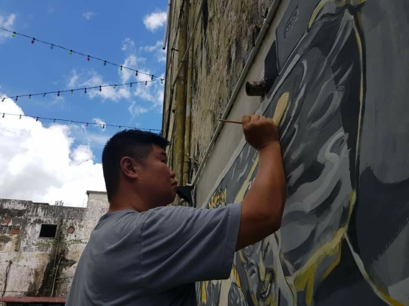 Mural artist Eric Lai would upkeep the pieces he drew at the back lane of Taman Jubilee weekly as he felt a sense of responsibility for it. — Picture via Facebook