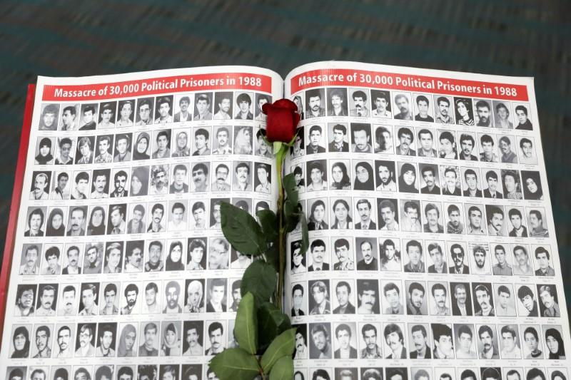 A rose rests on a page featuring photographs of people who have died in Iran as Iranian Americans from across California converge in Los Angeles