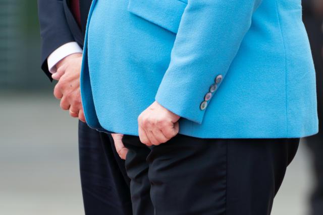 Angela Merkel presst während ihres Zitteranfalls beim Empfang von Finnlands Premier Rinne die Hände zusammen (Bild: Michael Kappeler/dpa)