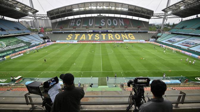 Juru kamera mengambil gambar saat pertandingan Jeonbuk Hyundai Motors melawan Suwon Samsung Blue Wings pada laga K-League di Stadion Jeonju, Korea Selatan, Jumat (8/5/2020). Kembali bergulir di tengah wabah corona, K-League tanpa penonton. (AFP/Jung Yeon-Je)