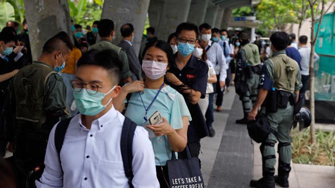 Polisi anti huru hara memeriksa kartu identitas pekerja di dekat Gedung Dewan Legislatif di Hong Kong, Rabu (27/5/2020). Penjagaan ekstra dilakukan menimbang kemungkinan aksi menentang RUU lagu nasional China dan rencana Beijing menerapkan UU keamanan nasional. (AP Photo/Kin Cheung)