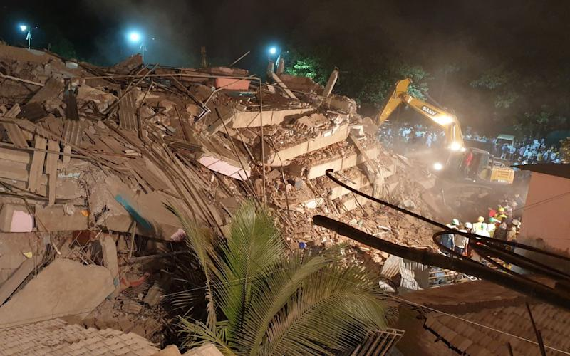 Rescue workers removes the debris as they look for survivors after a five-storey building collapsed in Mahad - Reuters
