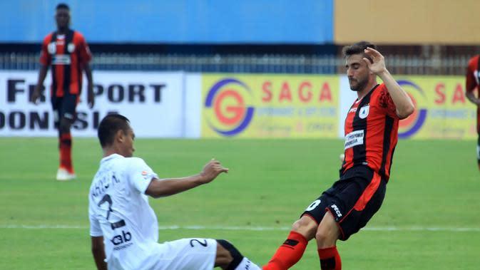 Pemain serbabisa Persipura Robertino Pugliara berduel dengan bek Bali United Wahyu Kristanto. (Liga Indonesia)