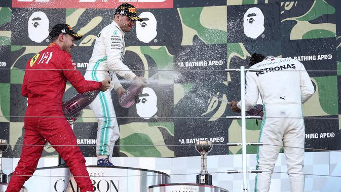 Pemenang F1 GP Jepang, pembalap Mercedes Valtteri Bottas Valtteri Bottas (tengah) bersama peringkat dua pembalap Ferrari, Sebastian Vettel menyemprotkan sampanye ke pembalap Mercedes Lewis Hamilton di atas podium Sirkuit Suzuka, Minggu (13/10/2019). (Behrouz MEHRI / AFP)