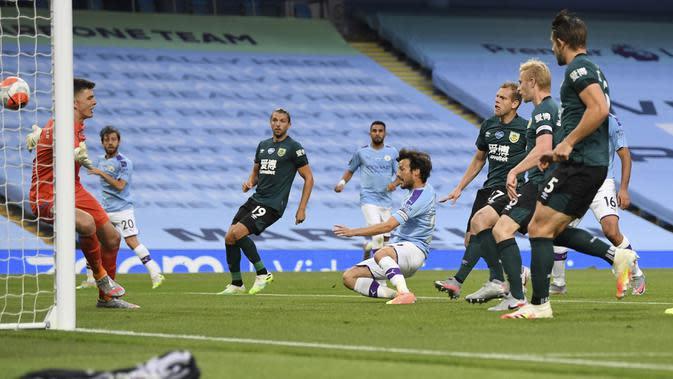 Pemain Manchester City, David Silva, mencetak gol ke gawang Burnley pada laga Premier League di Stadion Etihad, Senin (22/6/2020). Manchester City menang 5-0 atas Burnley. (AP/Shaun Botterill)