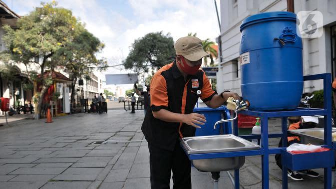 Petugas menyiapkan fasilitas cuci tangan yang disediakan di tiap pintu masuk kompleks wisata Kota Tua, Jakarta, Selasa (2/6/2020). Jelang berakhirnya PSBB di Jakarta, pengelola Kota Tua menyiapkan protokol kesehatan new normal bagi pengunjung. (merdeka.com/Iqbal S. Nugroho)