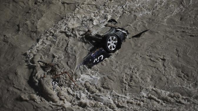 Sebuah mobil hanyut saat terjadi banjir di sungai Roya di Breil-sur-Roya, dekat perbatasan dengan Italia, Senin (5/10/2020). Banjir telah meluluhlantahkan daerah pegunungan di wilayah tenggara Perancis Alpes-Maritimes dan wilayah barat laut Italia. (AP Photo/Daniel Cole)